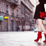 A girl with red bag and red boots in the street. Black coat.Beau